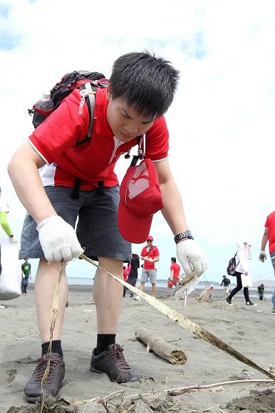 (圖說六) Canon企業志工在沙灘上仔細觀察並認真撿拾垃圾,為台灣的海岸環境與海洋保育盡一份心力。